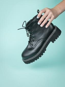 De hand van een vrouw houdt een brute leren schoen op een blauwe ondergrond