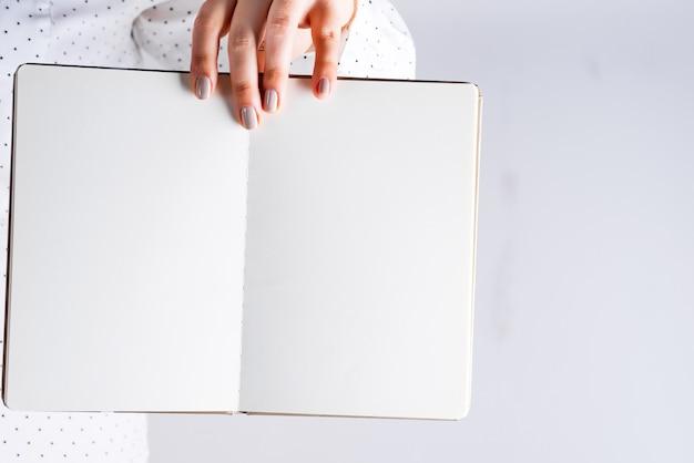 De hand van een vrouw houdt een gedetailleerd notitieboekje, de ruimte van het bedrijfsconceptenexemplaar