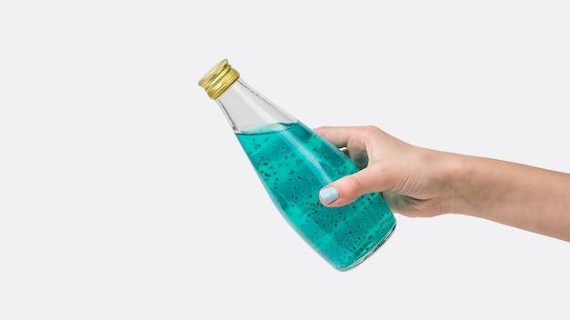 De hand van een vrouw houdt een gesloten fles met een blauwe cocktail en basilicumzaden die op een wit oppervlak worden geïsoleerd