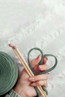 De hand van een vrouw houdt een groen breigaren vast en vouwt het in de vorm van een hart. begrip liefde voor breien en handwerk.