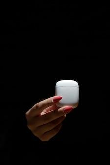 De hand van een vrouw houdt een hoesje voor draadloze hoofdtelefoons vast, de achtergrond is wazig