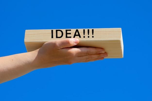 De hand van een vrouw houdt een houten blok vast met de tekst van idea tegen een blauwe lucht. het concept van succes en positief denken.