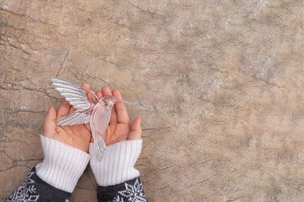 De hand van een vrouw houdt een kristallen kolibrie vast. kerstmis en nieuwjaar wenskaart concept. vintage-stijl.