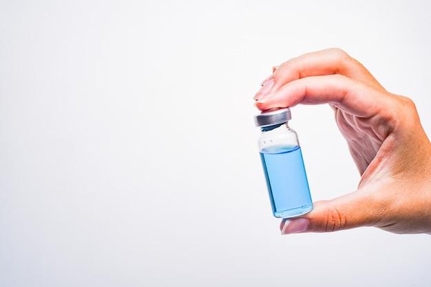 De hand van een vrouw houdt een medisch flesje of ampul vast. vaccin. de ampul met het medicijn. medicatie voor injectie.