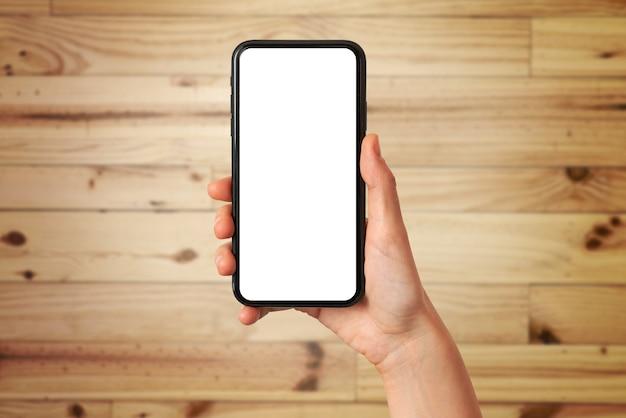 De hand van een vrouw houdt een mobiele telefoon vast met het lege scherm op een houten achtergrond