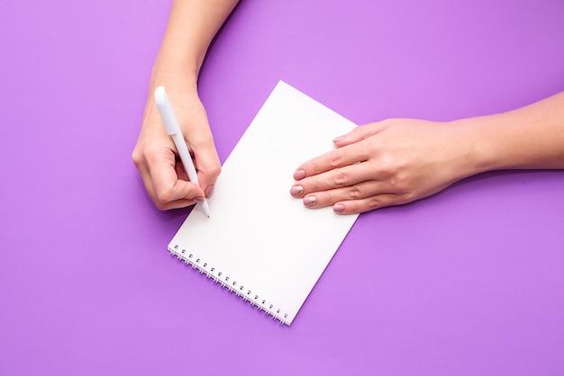 De hand van een vrouw houdt een notitieboekje met witte lakens op een lichte achtergrond. een plek voor tekst, een blik van bovenaf. plat leggen