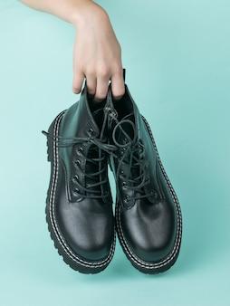 De hand van een vrouw houdt een paar zwarte leren schoenen op een blauwe ondergrond