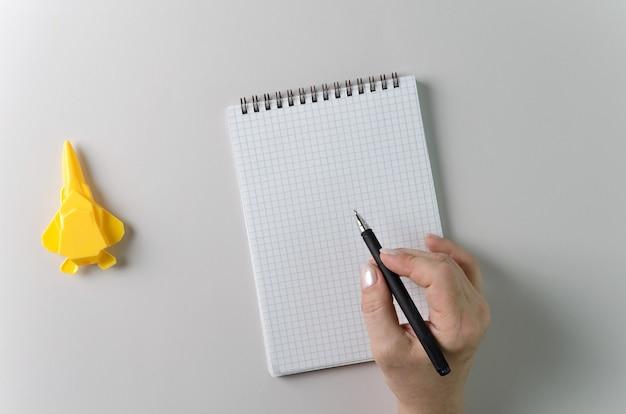 De hand van een vrouw houdt een pen en een spiraalvormig notitieboekje vast als lay-out voor uw ontwerp. grijze achtergrond, kopieer ruimte