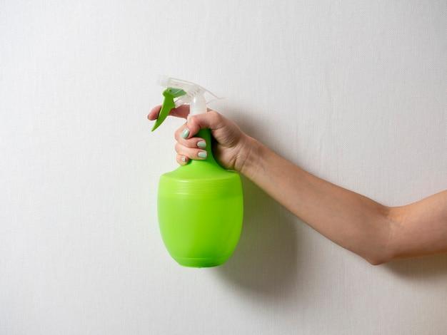 De hand van een vrouw houdt een plastic fles vast met een groene spuitfles op een grijze achtergrond. het concept van thuiszorg en schoonmaak.