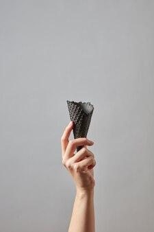 De hand van een vrouw houdt een scherpe lege zwarte wafelkegel op een donkergrijze muur met kopie ruimte voor uw zakelijke ideeën