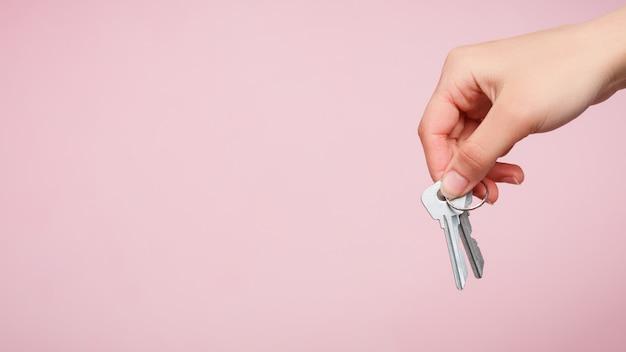 De hand van een vrouw houdt een sleutelbos vast.