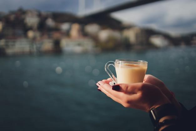 De hand van een vrouw houdt een witte kop warme melkachtige drank met kaneel vast, turkse salep sahlep genaamd, op de achtergrond van kabbelend water en de mistige maagdentoren in de verte, istanbul.