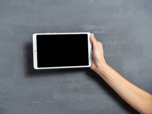 De hand van een vrouw houdt een witte tablet vast op een grijze gestructureerde achtergrond. plaats om op het scherm van een elektronische tablet in te voegen.