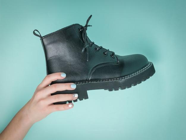 De hand van een vrouw houdt een zwarte schoen op een blauw oppervlak