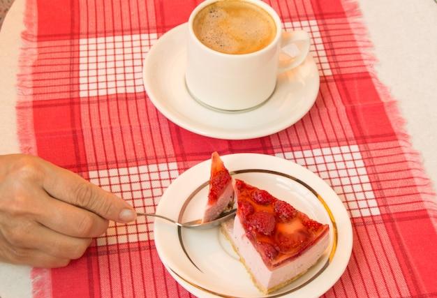 De hand van een vrouw houdt met plezier een stuk verse aardbeien-cheesecake vast, een kopje koffie op een schotel, een uitzicht van bovenaf. het concept van een heerlijk gastronomisch ontbijt.
