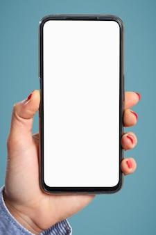 De hand van een vrouw houdt verticaal een smartphone vast met een leeg wit scherm op een blauwe achtergrond. voor de copyspace.