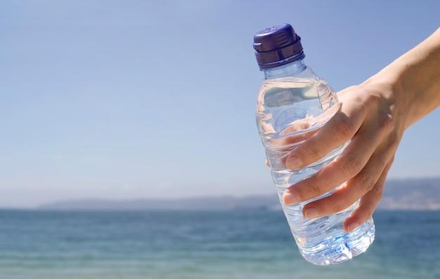 De hand van een vrouw met een fles koud water op het strand