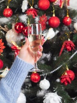 De hand van een vrouw met een glas champagne en een versierde kerstboom