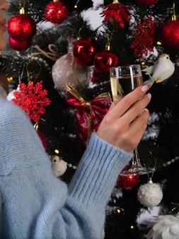 De hand van een vrouw met een glas champagne op de achtergrond van een versierde kerstboom