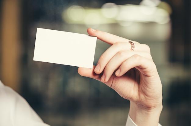 De hand van een vrouw met een visitekaartje.