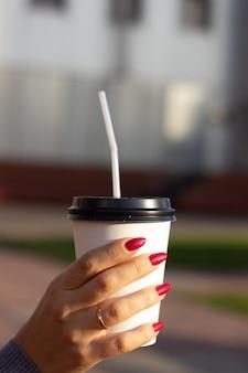 De hand van een vrouw met een witte koffiekopje.