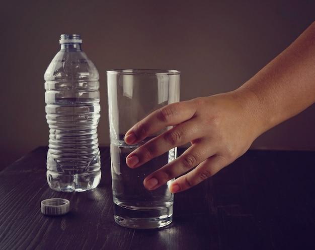 De hand van een vrouw neemt een glas water