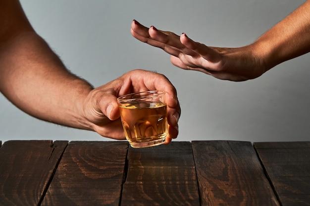 De hand van een vrouw probeert haar partner ervan te weerhouden om aan een bar te drinken. concept van alcoholisme en alcoholverslaving.