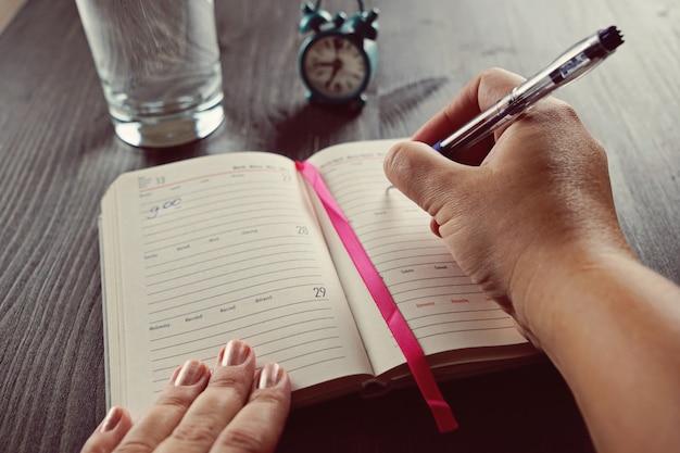 De hand van een vrouw schrijft in haar dagboek