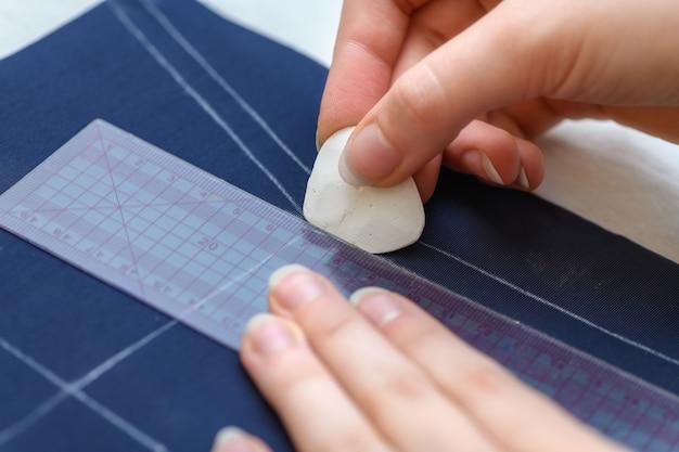De hand van een vrouw tekent lijn op de stof met krijt om een kledingstuk te knippen