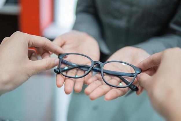 De hand van een winkelbediende geeft een bril aan de hand van een klant bij een opticien