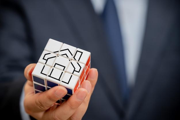 De hand van een zakenman die een kubus vasthoudt met uitzicht op het huispictogram.