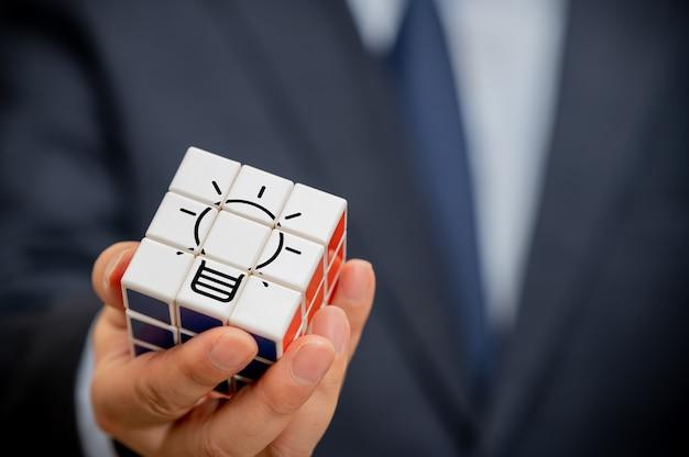 De hand van een zakenman die een kubus vasthoudt met uitzicht op het lamppictogram.