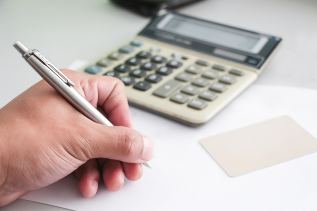 De hand van een zakenman die met pen wazige calculator en creditcard schrijft. werkend kantoorconcept. betalingsconcept. account of financieel. aankoop of koper concept.