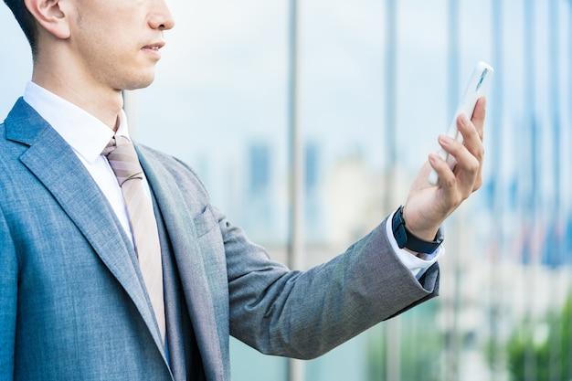 De hand van een zakenman in een pak met een smartphone