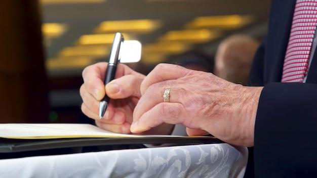 De hand van een zakenman ondertekent een belangrijk document met een pen