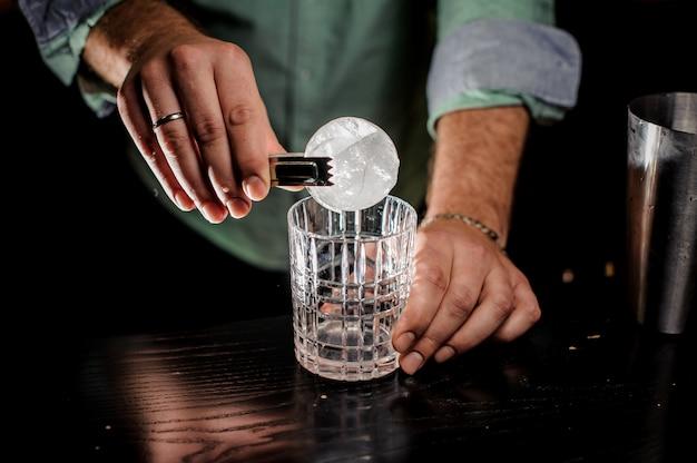 De hand van het bartendingconcept sneed ijsbal bij bar