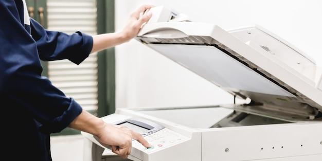 De hand van het bedrijfsmensentoetsenbord op de paneelprinter, printer, scanner, laserkopieerapparaat, kantoorbenodigdheden, concept, begint te werken