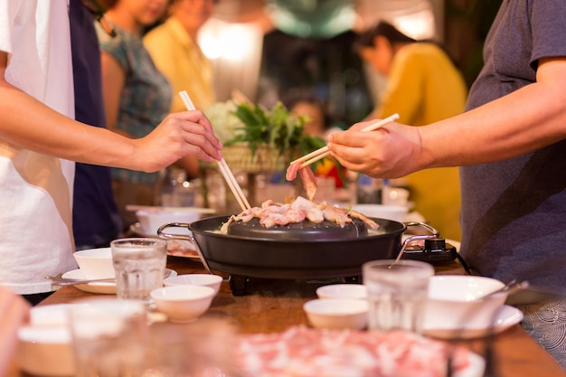 De hand van het familiediner met plak van het eetstokje de kokende varkensvlees op hete bbq pan.