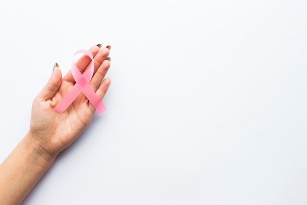De hand van het gewas met roze lint