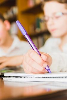 De hand van het gewassenkind die in schoolexemplaarboek schrijven