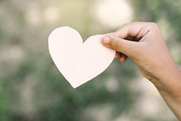 De hand van het kind houdt een hart vast.