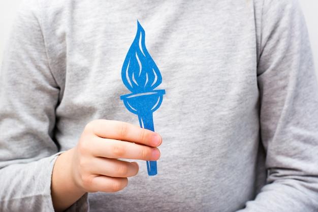 De hand van het kind houdt een zaklamp uit blauw karton gesneden