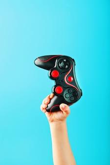 De hand van het kind houdt triomfantelijk de gamepad op een blauw oppervlak