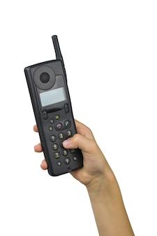 De hand van het kind kiest combinatie op retro telefoon die op witte achtergrond wordt geïsoleerd. retro communicatiemiddelen. technologie uit het verleden.