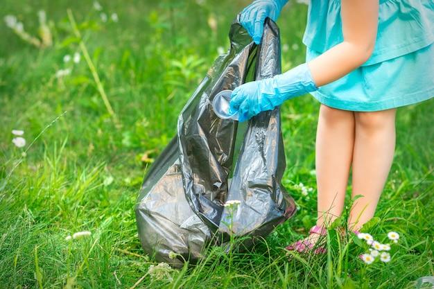 De hand van het kind legt plastic afval in de vuilniszak in het park