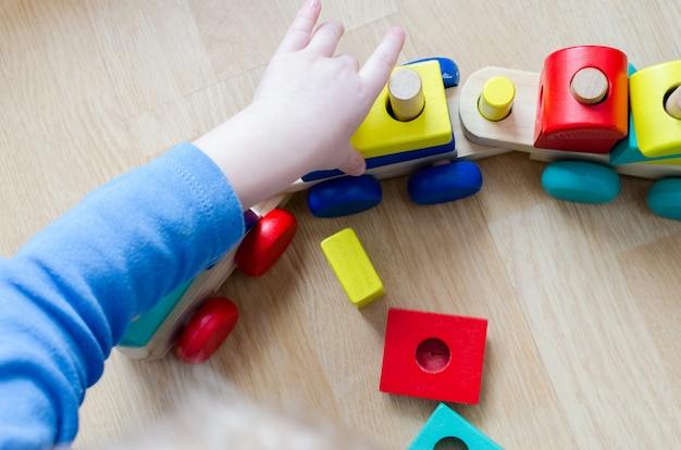 De hand van het kind met een stuk speelgoed