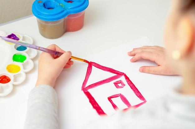 De hand van het kind met penseel tekenen van het huis op wit papier door aquarellen.