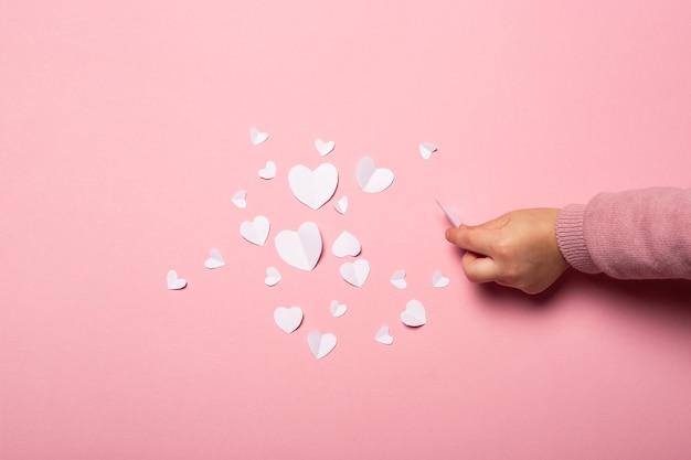 De hand van het kind neemt een valentijnskaart van papier op een roze achtergrond. samenstelling valentijnsdag. banner. plat lag, bovenaanzicht.