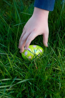 De hand van het kind ongeveer om een paasei op te nemen die in het gras wordt verborgen