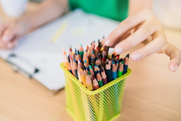 De hand van het kind pakt de kleurpotloden in een kleine doos om verder te kleuren in het werk.